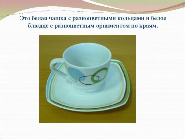 Это белая чашка с разноцветными кольцами и белое блюдце с разноцветным орнаментом по краям.