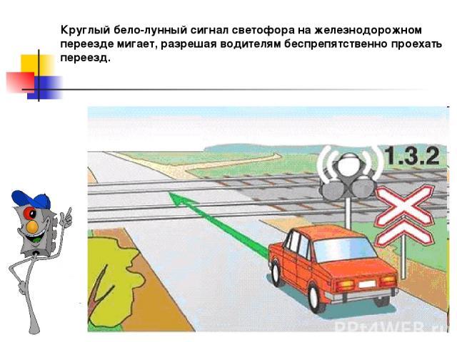 Круглый бело-лунный сигнал светофора на железнодорожном переезде мигает, разрешая водителям беспрепятственно проехать переезд.